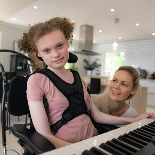 Amalie spiller piano med moren sin