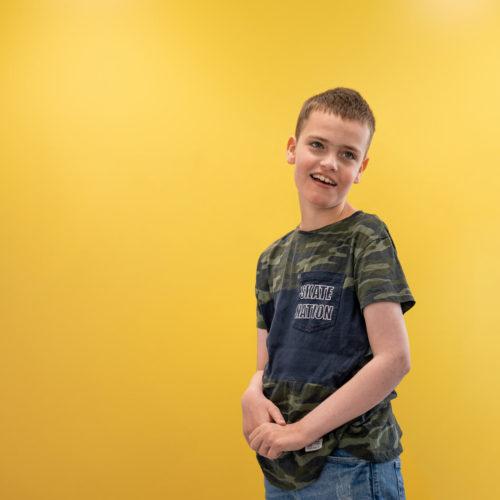 Lukas smiler foran en gul vegg
