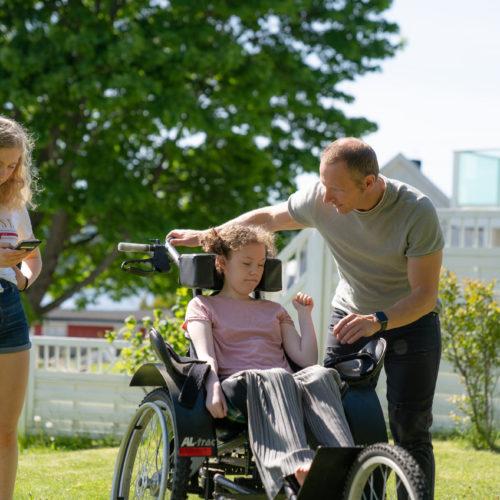 Amalie ute i hagen med pappa og søster